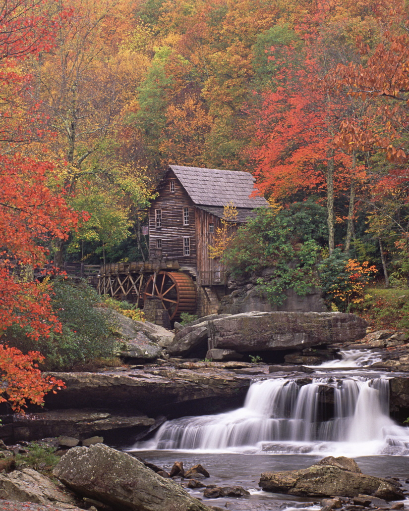 a historic grist mill building on the banks of gla 6MYHMPQ